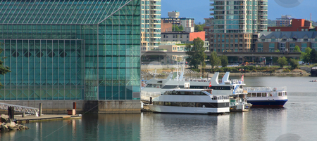 Waterfront Buildings and Boats stock photo, Several boats docked at a glass building, with the city in the background. by Steve Stedman