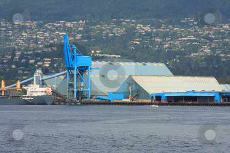 Shipping Port stock photo, Blue buildings and crane loading a ship in the port. by Steve Stedman
