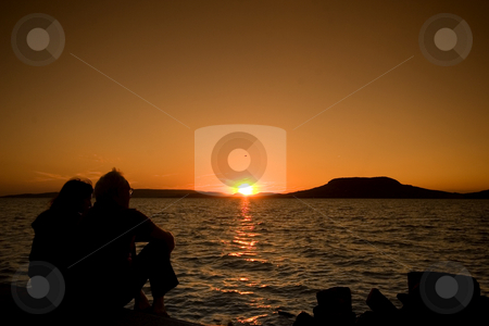 Couple at sunset stock photo, Balaton, calm, clouds, evening, freetime, hills, hungary, lake, lighthouse, mole, nautic, navigation, people, portside, quiet, reflection, relax, sea, starboard, sunset, tourist, travel, walking, water, waves, wind, windy by Fesus Robert