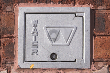 Water Meter Cover stock photo, The cover to a water meter supplying water to the masses. by Robert Byron