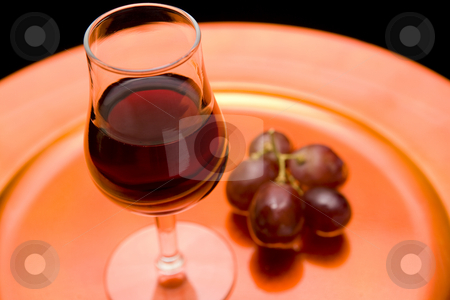 Red wine and grapes on a tray stock photo, Closeup of a glass of red wine and red grapes on an orange tray. Black backround by Magdalena Ascough