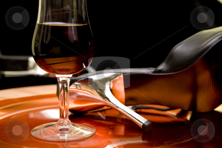 Red wine and high heels on a tray stock photo, Closeup of a glass of red wine and high heel shoes on an orange tray. by Magdalena Ascough