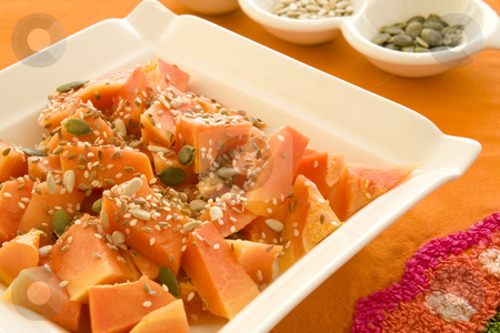Plate of papaya cubes and mixed seeds stock photo, Freshly cut papay cubes with mixed sunflower, pumpkin, sesame and lintseeds on a square white plate with on an orange tablecloth by Magdalena Ascough
