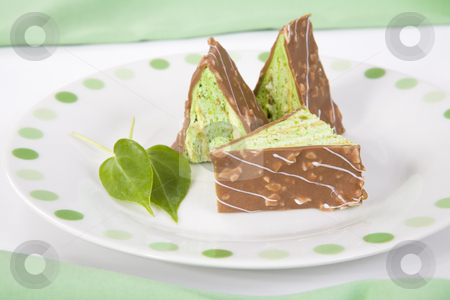Green triangle pieces of cake with chocolate on a plate stock photo, Three green triangular pieces of cake with chocolate on a green spotted plate by Magdalena Ascough