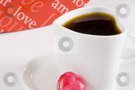 Coffee in white heart shape cup  stock photo, Freshly brewed coffee in white heart shape cup with words of love in background by Magdalena Ascough