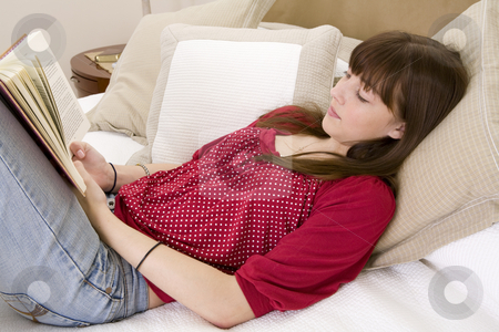 Teenager lying on bed reading a book stock photo, Teenager girl lying on bed relaxing and reading a book by Magdalena Ascough