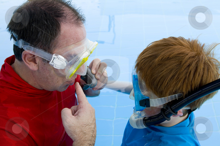 Father teaching his son how to use a mask and snorkel stock photo, A father teaching his son swim using a mask and snorkel in a swimming pool by Magdalena Ascough