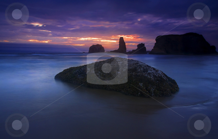 Hint of Light stock photo, A bit of light at sunset that only lasted for a few moments before the clouds closed in. Face rock in the distance as the waves of a minus tide surround the rocks along the Southern OREgon coast near Bandon. by Mike Dawson