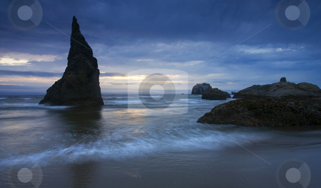 Last Light stock photo, A jagged seastack silhouetted against the last hint of light of the setting sun over the beach near Bandon, ORegon. by Mike Dawson