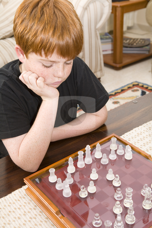 Red hair boy playing chess stock photo, A ten year old boy with red hair playing chess indoors by Magdalena Ascough