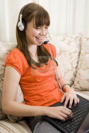 Teenager girl talking with headset and laptop stock photo, Closeup of a teenager girl sitting on a couch talking with a headset and laptop by Magdalena Ascough