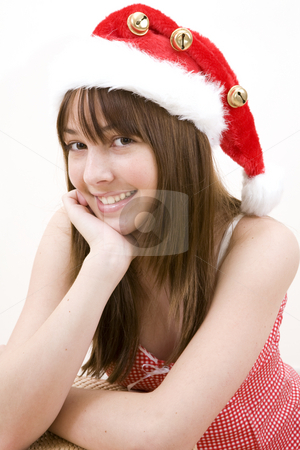 Teenager girl wearing a Christamas hat stock photo, Closeup of a teenager girl wearing a Christmas hat with fur and bells. White background by Magdalena Ascough