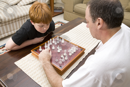 Father and son playing chess indoors stock photo, A father and 10 year old son playing chess indoors by Magdalena Ascough