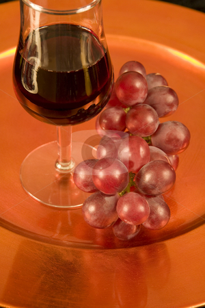 Red wine and red grapes on a tray stock photo, A tasting glass of red wine and grapes on a bronze tray. Black background. by Magdalena Ascough