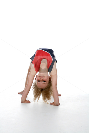 Cute girl in gymnastics bridge position over white stock photo, Young girl doing a gymnastics bridge position by Sue and Shawn Roberts