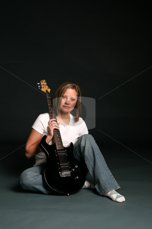 Pretty woman with guitar stock photo, Attractive woman sitting on the floor with an electric guitar. by Sue and Shawn Roberts