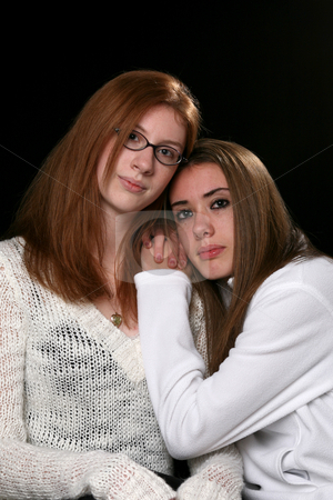 Two teenage girls leaning on one another stock photo, Two sisters in white sweaters, sitting together with their heads touching. by Sue and Shawn Roberts