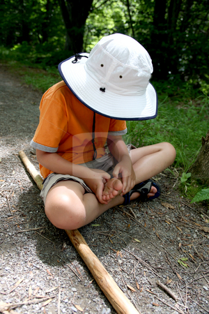 Young boy examining his foot stock photo, Young boy examining his foot on the hiking trail by Sue and Shawn Roberts