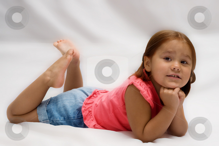 Female Child Portrait stock photo, A young girl lying on a soft white blanket getting her portrait done by Richard Nelson