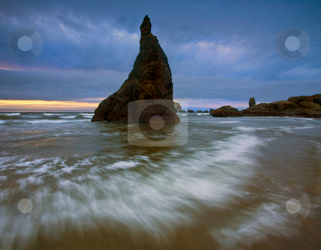 Storm Light stock photo, A stone seastack under stormy skies on the Oregon coast near Bandon. Just a hint of sunset light giving some warmth to the incoming tides. by Mike Dawson