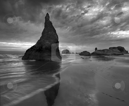 Reaching the Clouds stock photo, A seastack near Face Rock In Oregon pierces the clouds above as a summer storm passes. by Mike Dawson