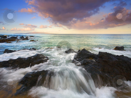 Water spilling over stock photo, The rising tide spilling over a large rock formation on the beach near Kihei on Maui at  sunrise. by Mike Dawson
