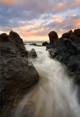 Primordial tides stock photo, Lava Rock formations off the South Coast of Maui with the pink glow of sunrise on the distant clouds. The dark rock against the colorful sky gave this a primordial feel to me hince he title! by Mike Dawson