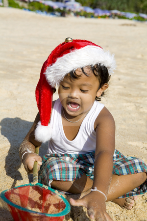 Thai boy with christmas hat on beach stock photo, Little Thai boy with christmas hat playing on beach by Magdalena Ascough