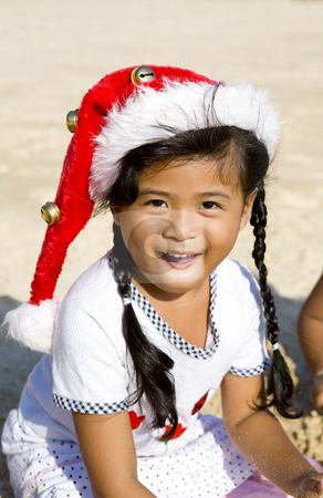 Thai girl with Christmas hat on beach stock photo, Thai girl with Christmas hat playing on beach by Magdalena Ascough