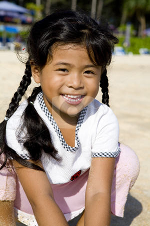 Thai girl on beach stock photo, Portrait on a little Thai girl on the beach by Magdalena Ascough