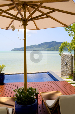Deck chair and white umbrella on patio stock photo, Deck chairs and white umbrella on a patio with a beautiful ocean view by Magdalena Ascough