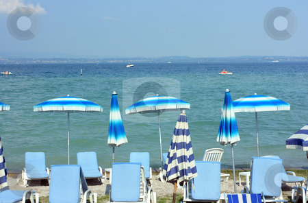 Summertime in Sirmione stock photo, Beach with colorful umbrellas in Sirmione near Garda lake by Natalia Macheda