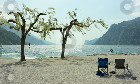 Chairs, trees, and surfers stock photo, Beautiful coastline of Garda lake in Torbole by Natalia Macheda