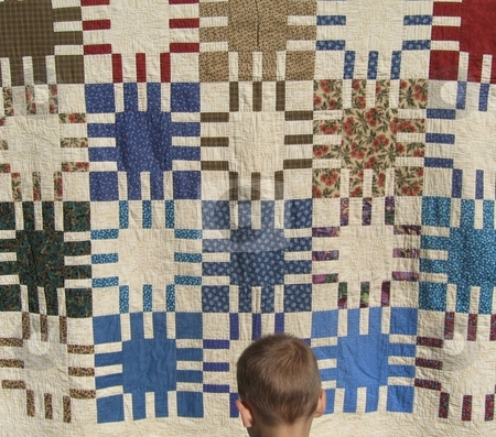 Boy and quilt stock photo, Young boy looks at vintage quilt by Becky Miller