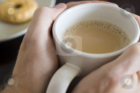 Warming hands stock photo, Warming hands on a large mug of white tea by Stephen Gibson