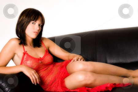 Laying down on a bencht stock photo, A brunette woman relaxing on a bench by Frenk and Danielle Kaufmann