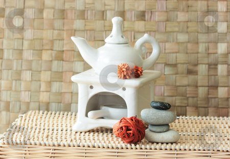 Aroma set stock photo, Fragrance lamp for meditation with dry aromatic flowers of orange color and a pile of zen stones by Natalia Macheda