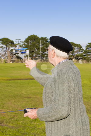 Child at heart stock photo, Elderly great-grandfather in his 80's, playing with a small remote controlled airoplane on a sportsfield. by Nicolaas Traut