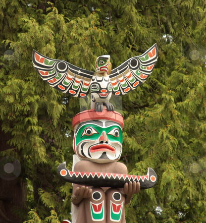 Totem Pole in Vancouver BC. stock photo, Historic totem pole with a bright face, canoe, and an eagle on top in Vancouver Canada. by Steve Stedman