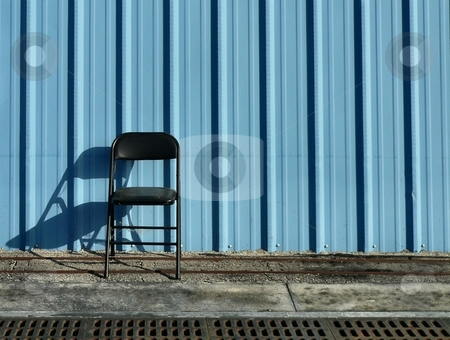Single chair stock photo, Single metal chair sitting in front of blue wall by Perry Correll
