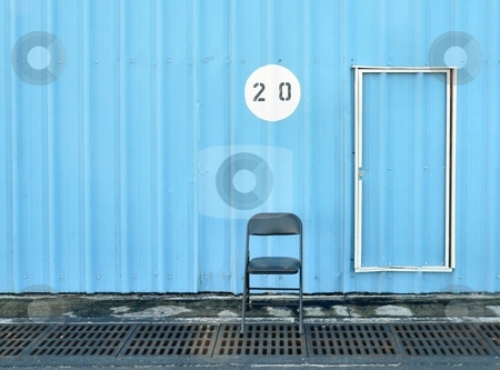 Chair and Door stock photo, Empty chair sitting next to closed door with building number above by Perry Correll