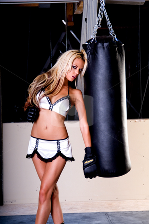 Sexy MMA Fighter stock photo, Sexy blond female MMA fighter leaning against the heavy bag while training in the gym by Robert Deal