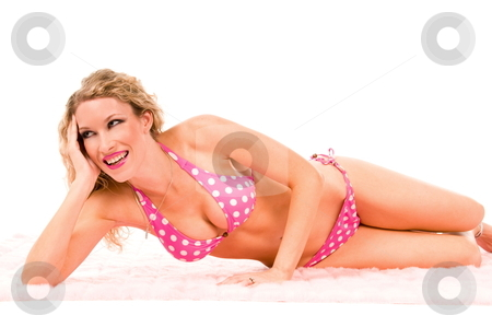 Happy woman in pink bikini. stock photo, Sexy smiling blond wearing a pink polka dot bikini laying on a the floor. by Robert Deal