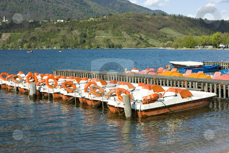 Catamarans on Caldonazzo lake stock photo, Row of colorful catamarans with buoys near wooden quay on Italian Caldonazzo lake near Trento by Natalia Macheda