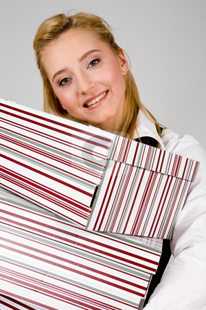 Smiling young woman with stack of boxes stock photo, Smiling young woman holding a stack of boxes indoors by Vitaly Sokolovskiy