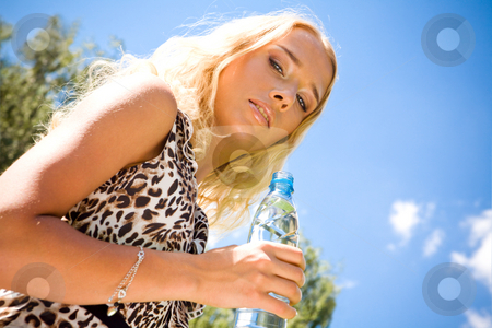 Lovely young woman with drink stock photo, Lovely young woman with bottle of water outdoors by Vitaly Sokolovskiy