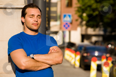 Caucasian man standing on the streets stock photo, Caucasian resting man standing on the streets by Vitaly Sokolovskiy