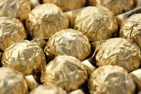 Chocolate sweets in golden foil stock photo, Chocolate sweets in golden foil. Focus on a central ball, shallow DOF by Natalia Macheda