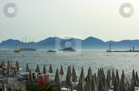 Cannes beach stock photo, Evening beach with closed umbrellas in Canness. View on the sea with yachts, lighthouse, and horizon ending up with hill silhouettes by Natalia Macheda
