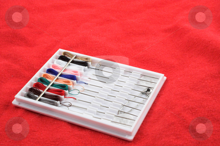 Sewing Kit on red background stock photo, A small portable travel sized sewing kit. by Robert Byron